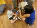 RMHCA guest children play with Hand in Paw dog