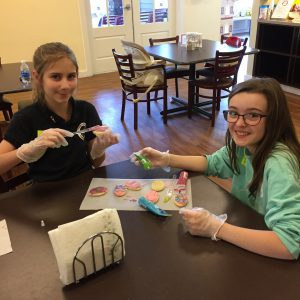 Two Prince of Peace students decorate cookies for Easter treats