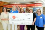 RMHCA and Children's of Alabama staff hold up a ceremonial check for the funds raised