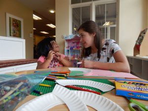 Abbie (left) helps one of the children make a craft.