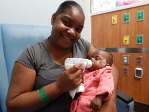 Ashley Harris feeds her daughter, E'mari.