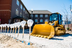 The construction zone at the Ronald McDonald House. The ground is dirt. Shovels and hard hats are displayed in front of a digger.
