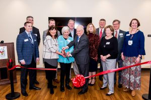 CEO Katherine Estes Billmeier, Co-Founder Marianne Sharbel and Board President Randy Nichols cut the ribbon on the $8.2 million expansion. They are surrounded by Board Members.