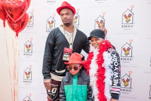 An RMHCA family gets silly at the photo booth with hats, glasses and feather boas!