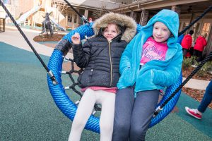 Raylee and Maddy Kate enjoy swinging on the playground.