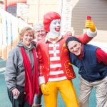 Volunteers from the Optimist Club take a picture with the Ronald statue in the courtyard.
