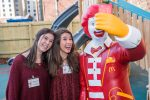 Two Student Leadership Council members pose for a picture with the Ronald statue on the playground.