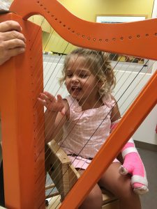 Cate plays the harp as part of her constraint therapy. Source: Capps family