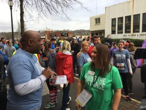 Jeh Jeh Pruitt from WBRC FOX6 News interviews RMHCA Communications Director Stephanie Langford. Behind them, 5K runners gather for their race.