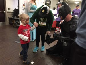 A young boy, who just had his face painted, says hello to Batman.
