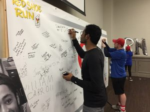 Two men sign the Heroes Wall, where runners can leave messages of encouragement for RMHCA families.