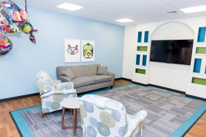 The Ronald McDonald Family Room at UAB sitting area includes two recliners and a couch set up around the TV.