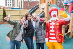Three girls take selfies with the Ronald McDonald statue outside in our playground.