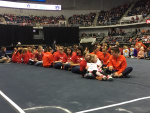 RMHCA kids sit on the elevated stage with Auburn gymnasts.