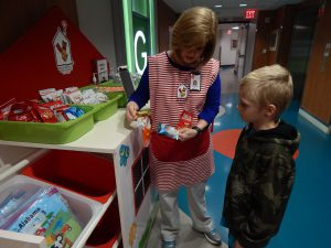 Volunteer Lisa Bolton tells a child about the available snacks on the Happy Wheels Cart.
