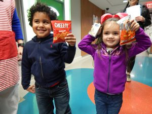 Two children show off the snacks they chose from the Happy Wheels Cart.