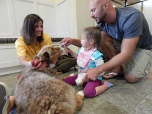 Daddy and daughter enjoy a visit from Hand in Paw.