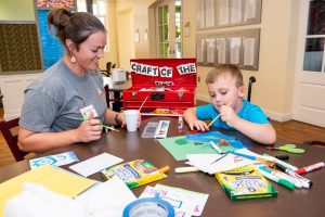 Volunteer Leigh Anne hosts the Art Cart with guest child Trenton Moore.