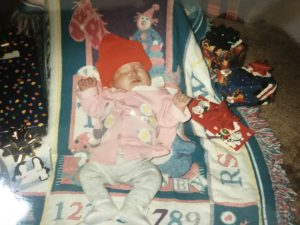 Baby Jana lies on a blanket. She is dressed in a white onsie, pink coat, and bright red beanie hat.