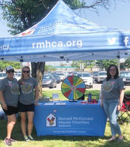 Intern stands (right) underneath RMHCA tent with 2 other RMHCA staff (left).