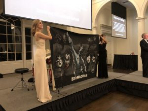 Two women hold up a one-of-a-kind KISS painting.
