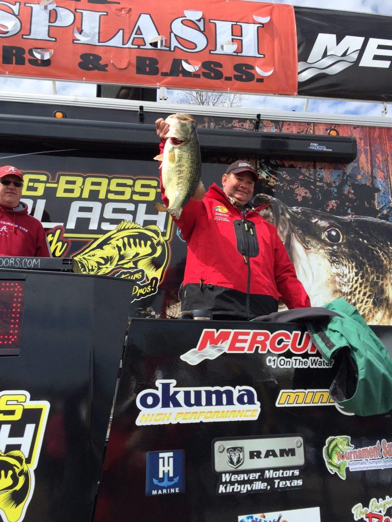 Man holds up a bass fish at Big Bass Splash