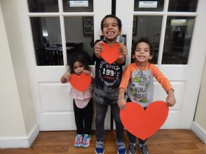 Watts family siblings holding hearts