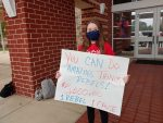 Student holds a sign promoting 1 Rebel 1 Cause
