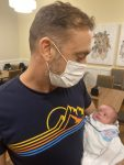 A father wearing a face mask holds his infant daughter
